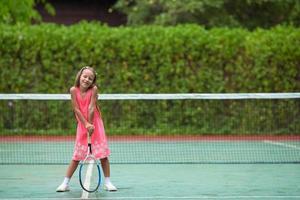 flicka poserar med en tennisracket foto