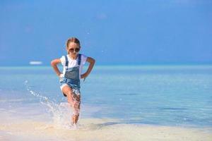 flicka som springer genom vatten på stranden foto
