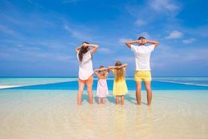 familj som kopplar av på en vit tropisk strand foto