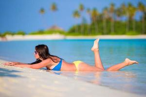 kvinna som lägger på stranden foto