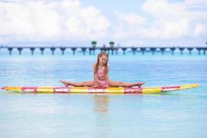 flicka poserar på en surfbräda