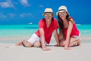par i röda skjortor på en strand foto