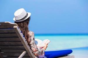 kvinna som läser en bok på stranden foto