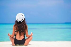 kvinna som mediterar på stranden