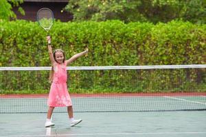 flicka som har kul att spela tennis foto