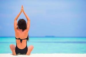 kvinna som utövar yoga på stranden