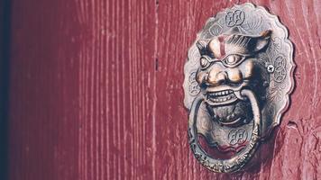 en röd dörr med dörrhandtag av kopparlejonhuvud foto