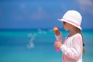 flicka som blåser bubblor på stranden