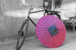 svartvit cykel med rött paraply foto