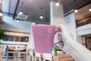 person som håller en kaffekopp foto