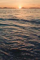 vacker solnedgång och havsvågor foto