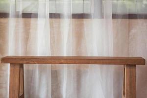 träbänk mot en fönsterridå foto