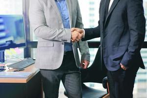 affärsmän som gör handslag på kontoret