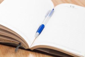 anteckningsbok med en blå penna
