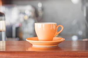 orange kaffekopp på ett kafé