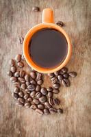 kaffebönor med en kaffekopp på ett träbord