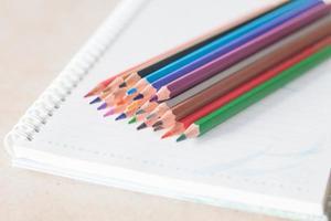 närbild av färgglada pennor på en spiralanteckningsbok foto