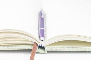 närbild av en öppnad anteckningsbok och penna foto