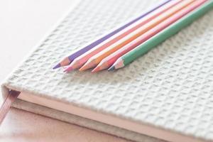 närbild av färgglada pennor på en grön anteckningsbok foto