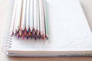 bunt med färgglada pennor på en spiralanteckningsbok foto