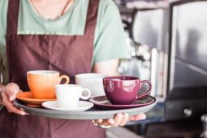 server som håller en bricka med kaffe