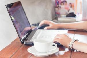 kvinna som använder en bärbar dator i ett kafé