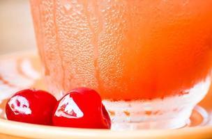 röda körsbär nära ett glas foto