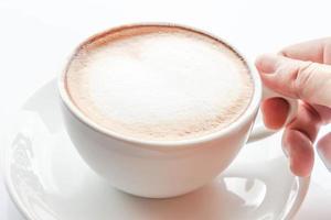 närbild av en hand på kopp latte