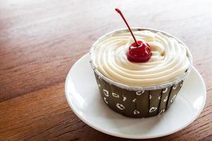 muffin med rött körsbär på en vit platta foto