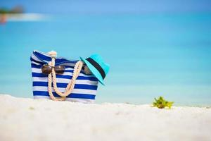 väska med solglasögon och hatt på en strand