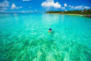 man snorklar i klart tropiskt vatten