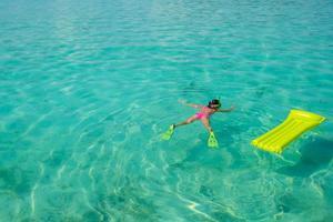 kvinna som snorklar i tropiskt vatten foto