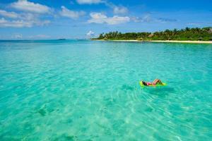 kvinna som kopplar av i vattnet på en tropisk strand