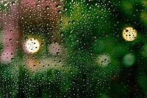 regndroppar på fönstret med färgglad bokeh foto