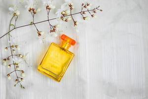 parfymflaskor och blommor på en vacker vit bakgrund foto