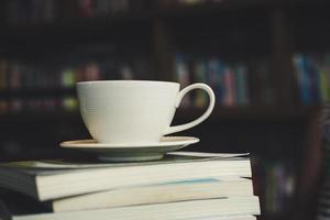 kaffekopp och bunt med böcker på träbord