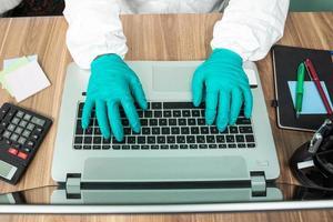 person i skyddsdräkt som arbetar på datorn