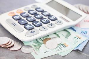 närbild av miniräknare och pengar foto