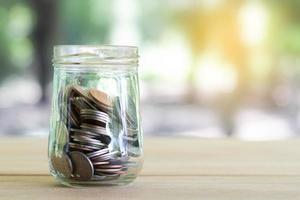 mynt på träbord med mjukt ljus