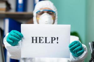 person i skyddande kostym som håller hjälpordet på kontoret foto