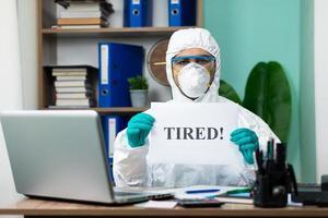 person i skyddande kostym som arbetar på bärbara datorn på kontoret foto