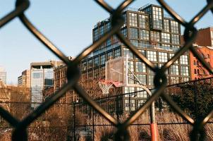 new york city, new york, 2020 - utsikt över en basketplan genom ett staket