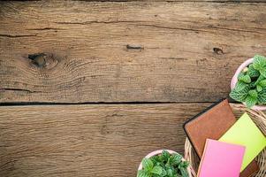 träskrivbord med anteckningsbok och blomma foto
