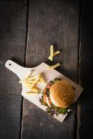 ovanifrån av rustik hemlagad hamburgare och pommes frites