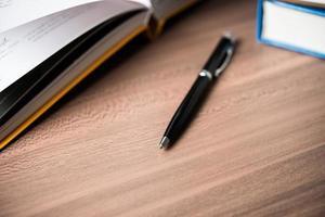 böcker med en penna på träbord foto
