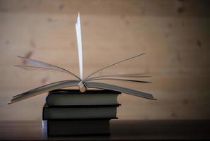 bunt med öppna böcker på ett träbord foto