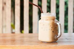 glas iskaffe på ett träbord utanför foto