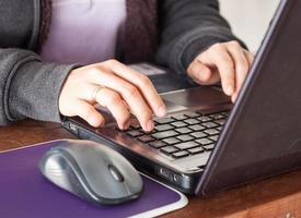 kvinna som använder bärbara datorn på kontorsskrivbordet