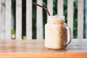 glas iskaffe på ett träbord på ett kafé foto