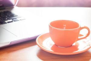 bärbar dator och kaffe på ett skrivbord foto